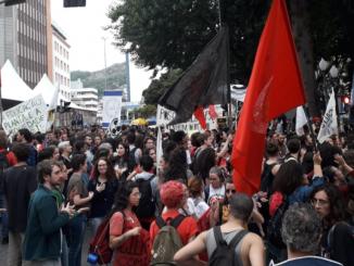 Na foto, manifestantes passam com cartazes, faixas e bandeiras na Marcha pela Educação e Ciência em frente a Catedral de Florianópolis.