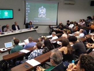 Foto dos conselheiros do Conselho Universitário sentados ouvindo o reitor na sala dos conselhos.