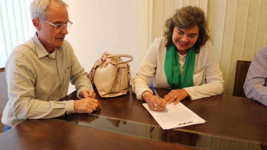 Professora Elisete Phitscher assina ata da posse ao lado do presidente da Apufsc, Bebeto Marques