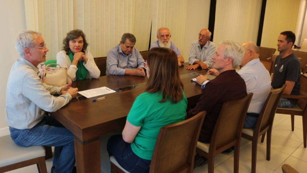 Membros do conselho fiscal sentados em uma mesa ouvem o presidente da Apufsc Bebeto Marques.