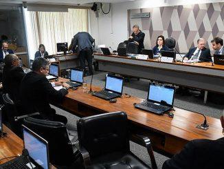 Imagem interna da sala da CCJ. Mesas retangulares com computadores em cima virados para uma mesa no início da sala, onde estão os relatores.