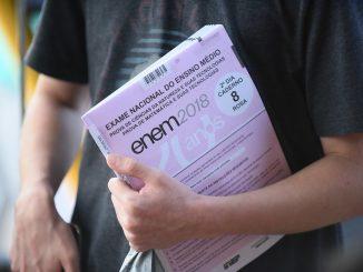 Jovem carrega um caderno de prova do Enem debaixo do braço esquerdo.