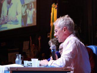 Presidente da Apufsc, Bebeto Marques, falando ao microfone no auditório Garapuvu, na UFSC.