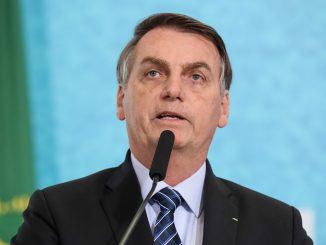 Foto do presidente Jair Bolsonaro falando no microfone.