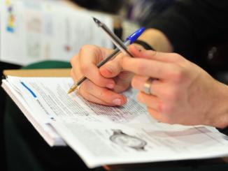 Na foto, um estudantes com canetas nas mãos apoiadas sobre a prova do Enem.