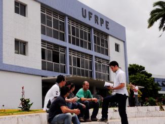 No fundo da imagem um dos prédios da UFRPE e no primeiro plano um grupo de alunos conversando.