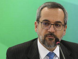 Na foto, o Ministro da Educação em frente ao microfone. O fundo da imagem é verde.