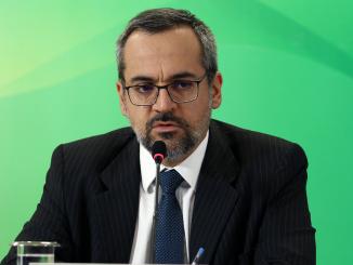 Ministro da Educação, Abraham Weintraub, sentado em frente ao microfone. No fundo, tons esverdeados.