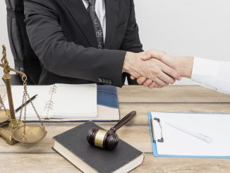 Foto genérica de um advogado apertando a mão do cliente.
