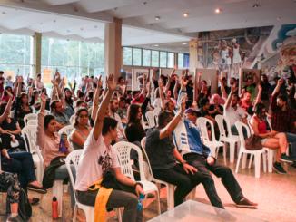 Técnicos administrativos da UFSC participam da assembleia no hall da reitoria onde acontece a votação para a paralisação nacional de 48 horas. Os TAE's a favor levantam a mão para votar.