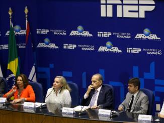 Na foto, integrantes de órgãos ligados a educação divulgam resultados do Enade 2018. Todos estão sentados em frente aos microfones. Atrás um fundo azul estampa os logotipos do Inep e do Governo Federal.