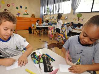 Duas crianças brincam com lápis de cor em uma mesa. Ao fundo, é possível ver uma sala de aula do Ensino Infantil com outras crianças.