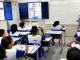 Crianças sentadas em uma sala de aula do ensino básico. Uma professora está à frente, próxima à lousa