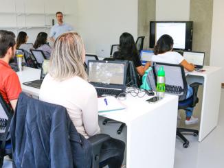 Estudantes da USP em frente a computadores durante uma aula.