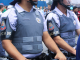 Na foto, dois policiais um ao lado do outro com colete à prova de balas e capacete. A fotografia corta a imagem do rosto dos policiais.