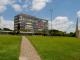 Prédio da reitoria da UFMG com um gramado no primeiro plano da foto.