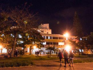 Centro de Comunicação e Expressão (CCE) da UFSC durante a noite. Algumas pessoas transitam pelo caminho em frente à Praça da Cidadania