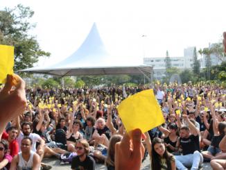 Estudantes da UFSC votam pela adesão a greve por tempo indeterminado. Em frente à reitoria, estudantes a favor levantam fichas amarelas para sinalizar seu voto.