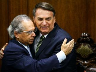 Presidente Jair Bolsonaro e ministro Paulo Guedes se abraçam