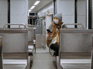 Mulher sozinha usando máscara no transporte público, durante pandemia de coronavírus. Lê notícias no celular. Foto: Canva